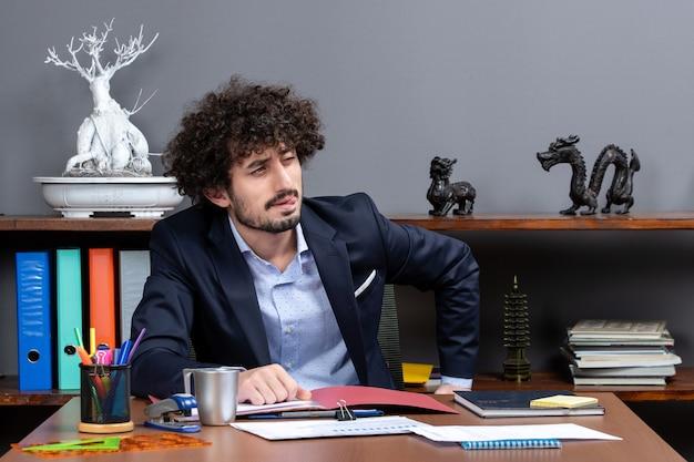 Vooraanzicht van jonge zakenman knipperend oog zittend aan de balie in kantoor