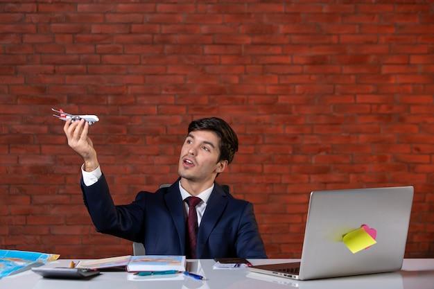 Vooraanzicht van jonge zakenman zittend achter zijn werkplek in pak werkplan aannemer project bedrijf baan bouwers bezetting corporate