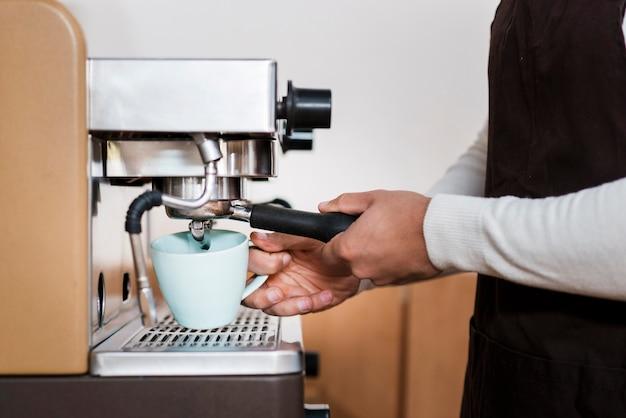 Vooraanzicht van jongen die espresso maakt