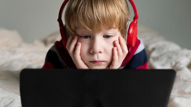 Vooraanzicht van jongen die tablet met hoofdtelefoons gebruikt
