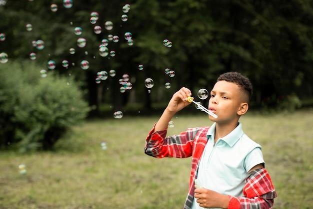 Vooraanzicht van jongen die zeepbellen maakt
