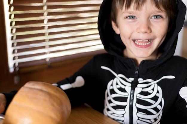Vooraanzicht van jongen met het concept van het pompoenkostuum