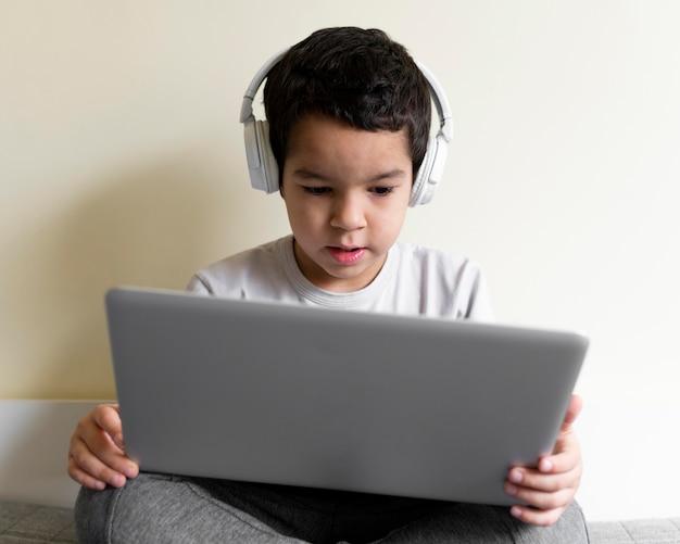 Vooraanzicht van jongen met laptop in bed
