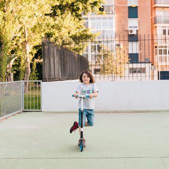 Vooraanzicht van jongen op scooter