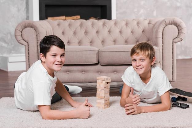 Vooraanzicht van jongens die een spel op vloer spelen