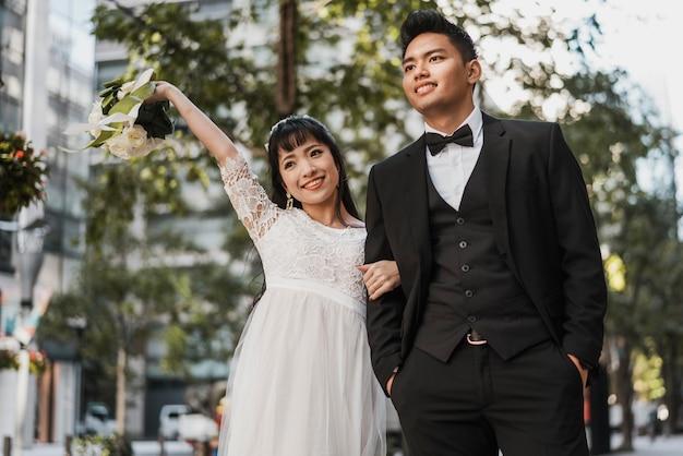 Vooraanzicht van jonggehuwden die buitenshuis glimlachen