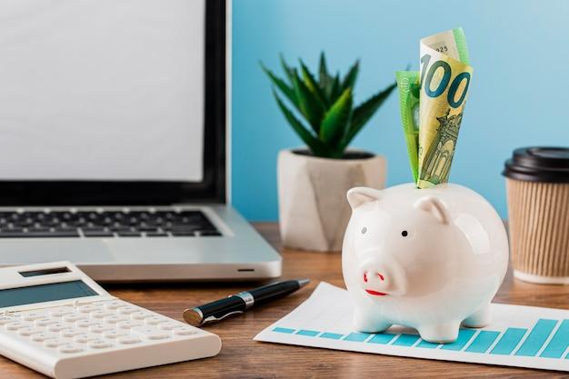 Vooraanzicht van kantoorartikelen met groeigrafiek en spaarvarken