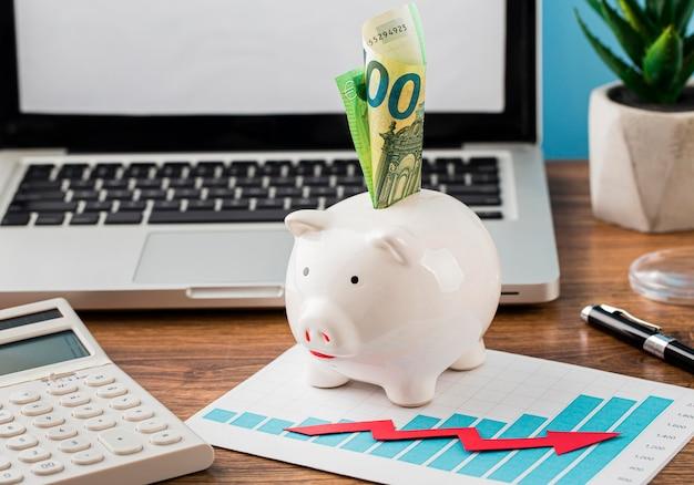 Vooraanzicht van kantoorartikelen met spaarvarken en groeigrafiek