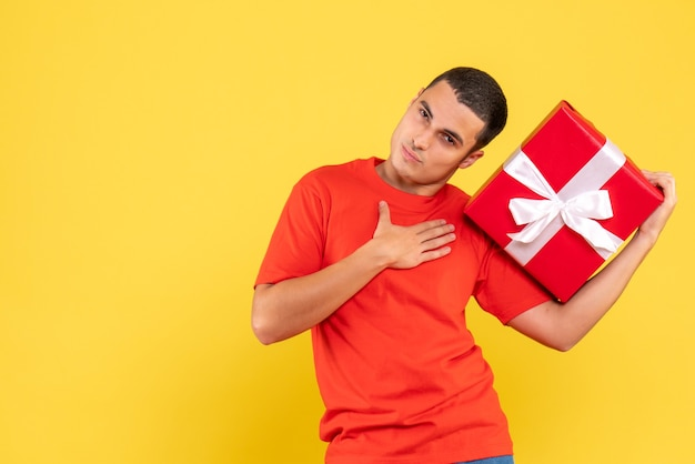 Vooraanzicht van kerstmis van de jonge mensenholding op gele muur