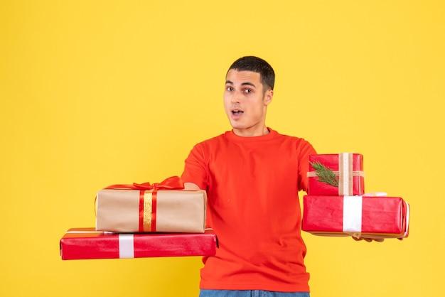 Vooraanzicht van kerstmis van de jonge mensenholding stelt op gele muur voor