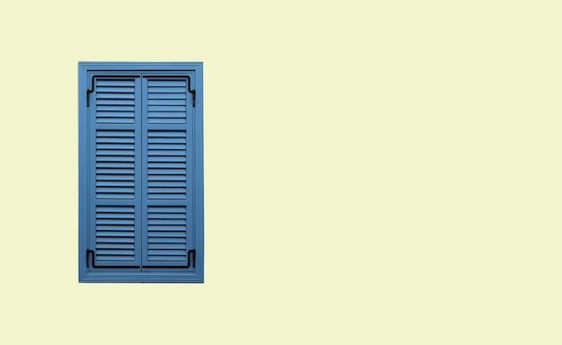 Vooraanzicht van keurig blauw venster met gesloten gestreepte luiken op beige gepleisterde muur