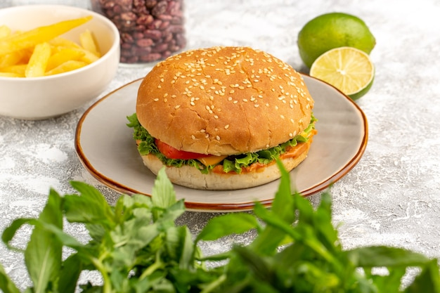 Vooraanzicht van kippensandwich met groene salade en groenten binnen met de citroen van frietenbonen op wit bureau