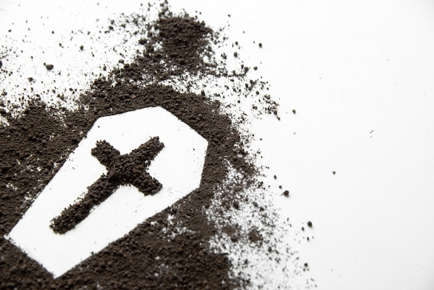 Vooraanzicht van kistvorm met donkere grond en kruis op wit oppervlak