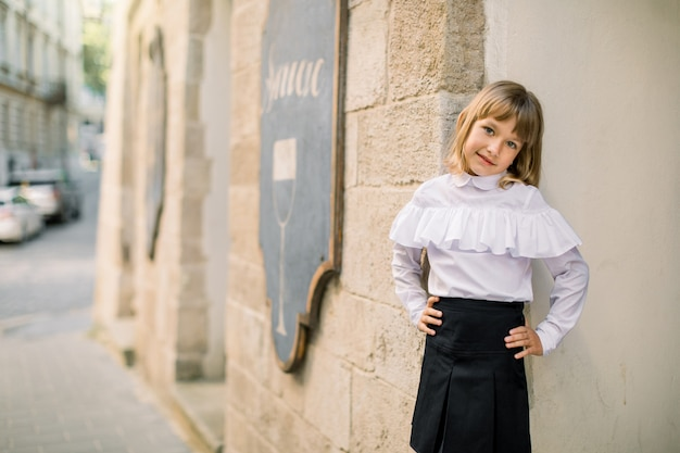 Vooraanzicht van klein blond meisje in zwart-witte kleren poseren in de straat stad tegen de achtergrond van de muur van het oude gebouw