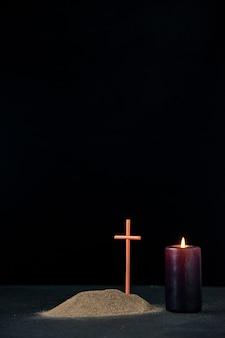 Vooraanzicht van klein graf met brandende kaars op zwart