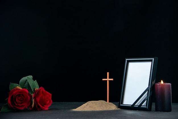 Vooraanzicht van klein graf met kaars en fotolijst op zwart