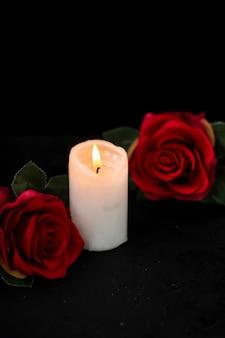 Vooraanzicht van klein graf met kaars en rode rozen op zwart