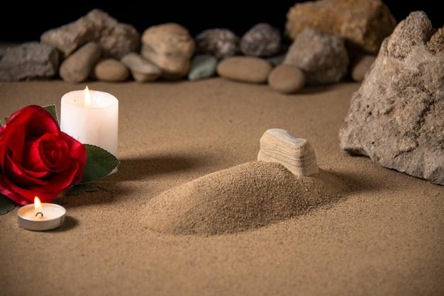 Vooraanzicht van klein graf met kaars en stenen op zand