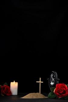 Vooraanzicht van klein graf met kaars rode roos op zwart