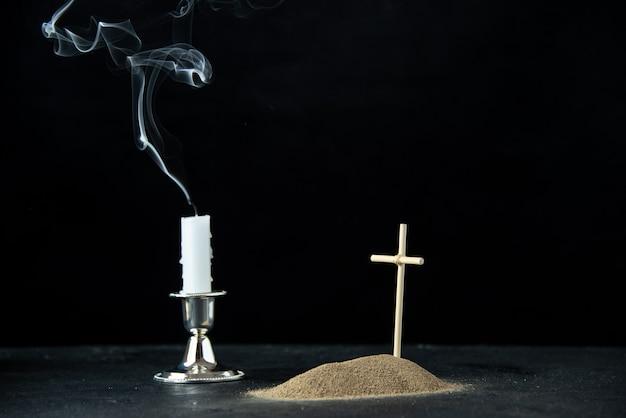 Vooraanzicht van klein graf met kaarsen op de zwarte
