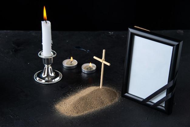 Vooraanzicht van klein graf met kruis en fotolijst op donker