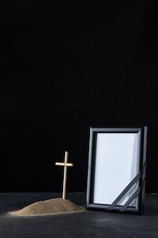 Vooraanzicht van klein graf met kruis en fotolijst op zwart