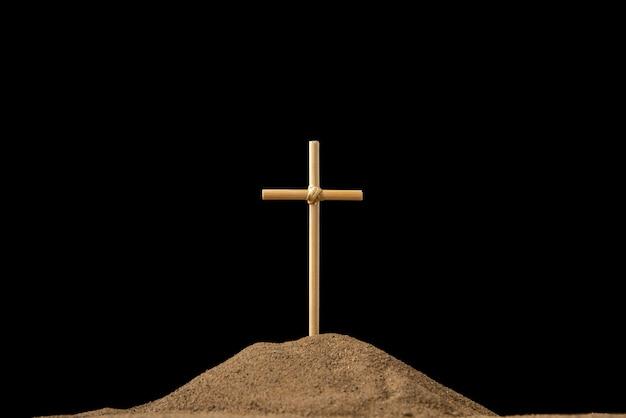 Vooraanzicht van klein graf met kruis op dark