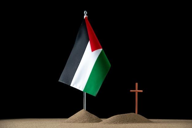 Vooraanzicht van klein graf met palestijnse vlag op zwart