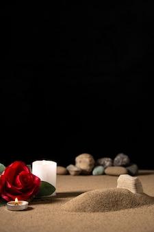 Vooraanzicht van klein graf met rode bloem en kaars op zanddood