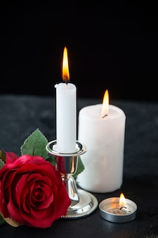 Vooraanzicht van klein graf met rode roos en kaars op zwart