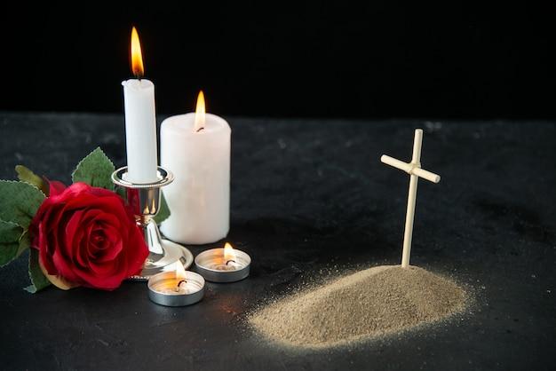Vooraanzicht van klein graf met rode roos en kaarsen op zwart