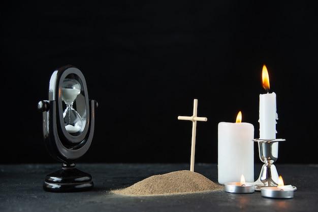 Vooraanzicht van klein graf met zandloper en kaarsen op dark