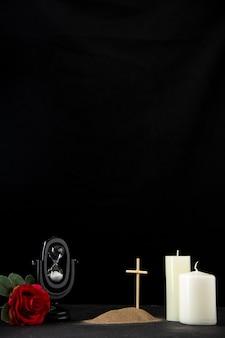 Vooraanzicht van klein graf met zandloper en rode roos op zwart