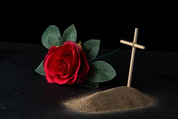 Vooraanzicht van klein graf van zand met stokkruis op zwart