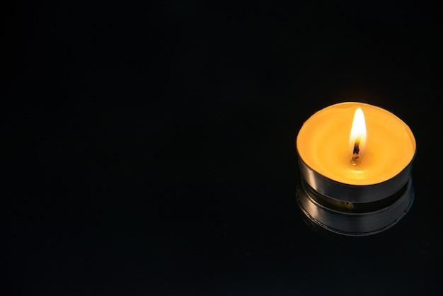 Vooraanzicht van kleine brandende kaars op zwart