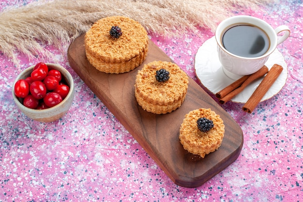 Vooraanzicht van kleine heerlijke taarten ronde gevormd met kaneel en thee op het roze oppervlak