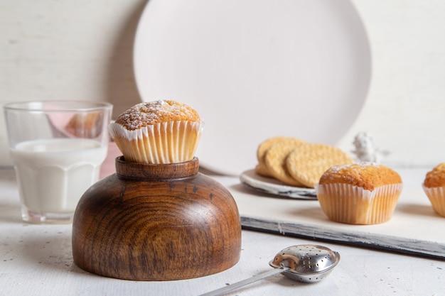 Vooraanzicht van kleine lekkere taarten met suiker poeder melk en koekjes op de witte ondergrond