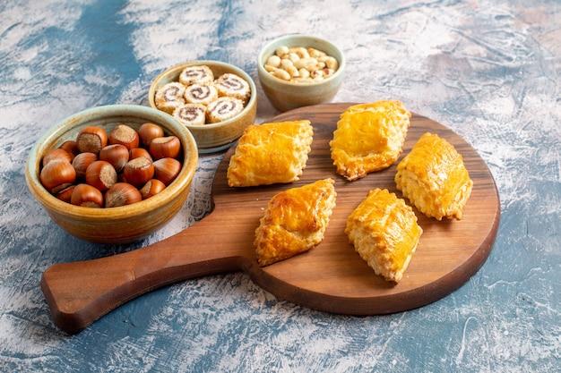 Vooraanzicht van kleine zoete gebakjes met noten op blauwe ondergrond