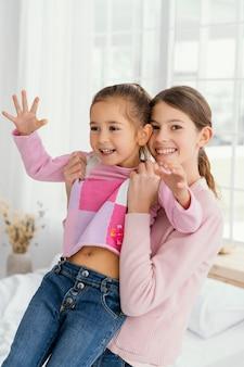 Vooraanzicht van kleine zusjes samen thuis Premium Foto