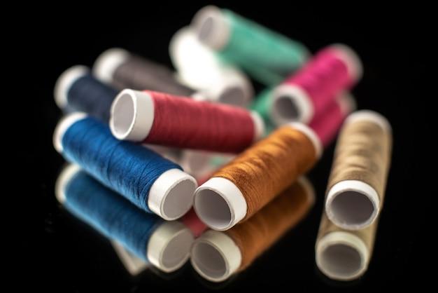 Vooraanzicht van kleurrijke draden op donkere ondergrond
