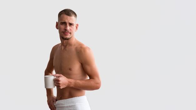 Vooraanzicht van knap in de ochtend met koffie en exemplaarruimte