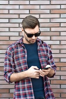 Vooraanzicht van knappe jonge man in slimme vrijetijdskleding houdt een mobiele telefoon terwijl hij op de bakstenen muur achtergrond staat.