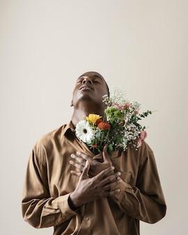 Vooraanzicht van knappe man poseren met boeket bloemen