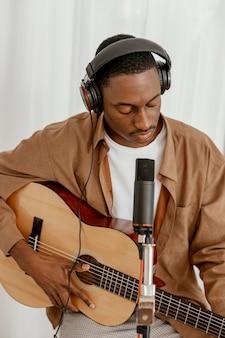 Vooraanzicht van knappe mannelijke musicus die thuis gitaar speelt