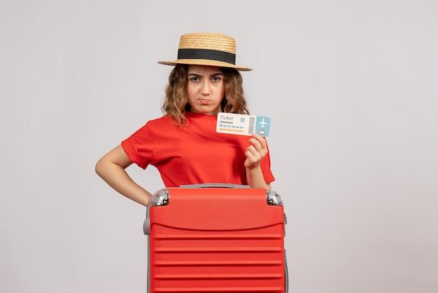 Vooraanzicht van knorrig vakantiemeisje met haar valise holdingskaartje