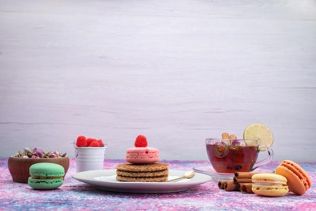 Vooraanzicht van koekjes en macarons met thee en kaneel op het lichte bureau
