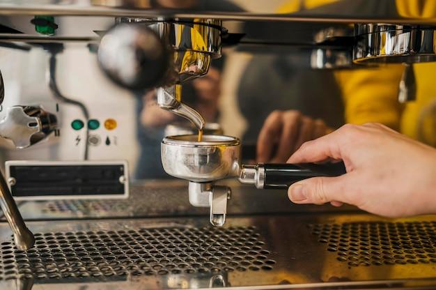 Vooraanzicht van kopje koffie machine gehouden door barista