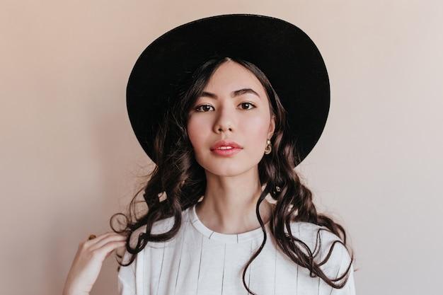 Vooraanzicht van krullende koreaanse vrouw. studio shot van mooie aziatische vrouw geïsoleerd op beige achtergrond.
