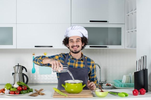 Vooraanzicht van lachende en positieve chef-kok met verse groenten die water toevoegen aan de pot in de witte keuken