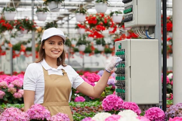 Vooraanzicht van lachende jonge vrouw in beige schort werken in moderne grote kas met speciale technologie. concept proceswerk met bloemen in broeikas.